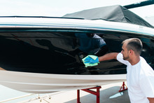 Boat Maintenance - A Man Cleaning Boat With Cloth. Selective Focus.