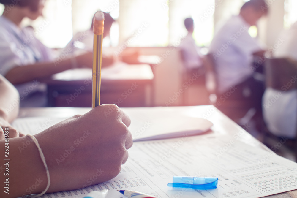 Fotografía Close up to hand of student is taking exam and writing answer in classroom for e