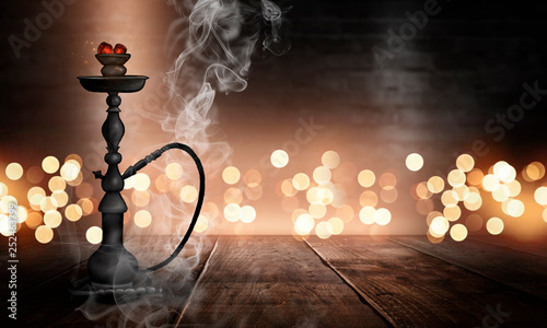 Photo  Hookah in a dark room with smoke, abstract bokeh light, wooden table, wet asphalt, reflection