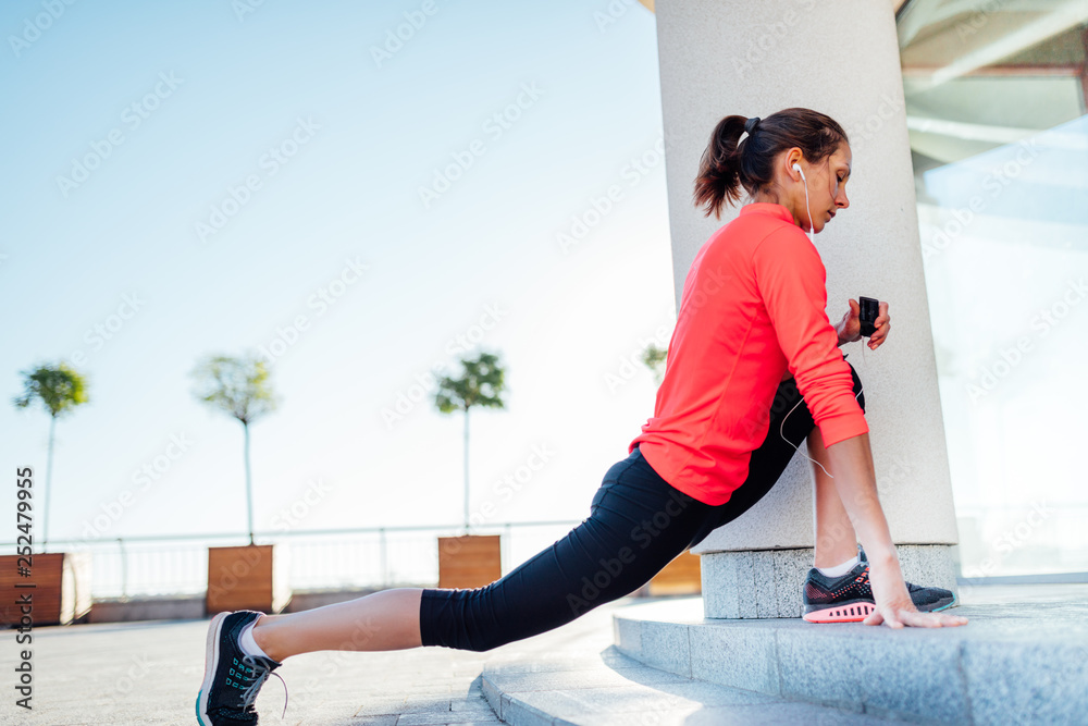 Fototapeta Young woman listening music while stretching before jogging exercise