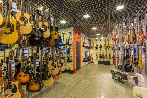 Foto op Canvas Muziekwinkel A row of different electric guitars hanging in a modern musical shop