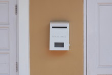 White Mailbox Between White Wooden Door And Window On Brown Painted Wall Of House, Home Exterior Decoration Concept