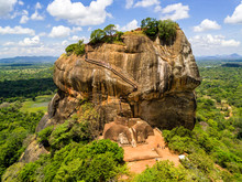 Aerial View From Above Of Sigiriya Or The Lion Rock, An Ancient Fortress And A Palace With Gardens, Pools, And Terraces Atop Of Granite Rock In Dambulla, Sri Lanka. Surrounding Jungles And Landscape
