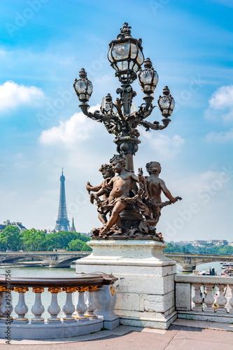 Valokuva  Street lamp on Alexander III bridge and Eiffel Tower at background, Paris, Franc