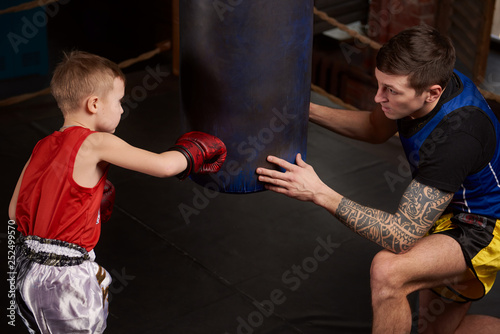 Child strikes hand over boxing bag and coach teaches right