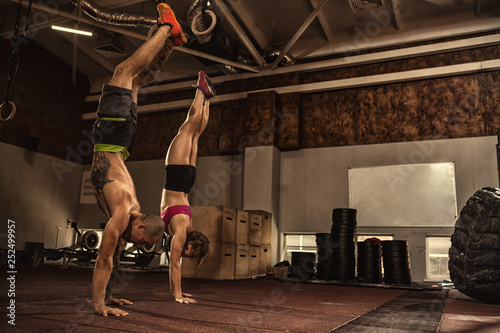 Photo Athletic young couple doing a handstand at the gym