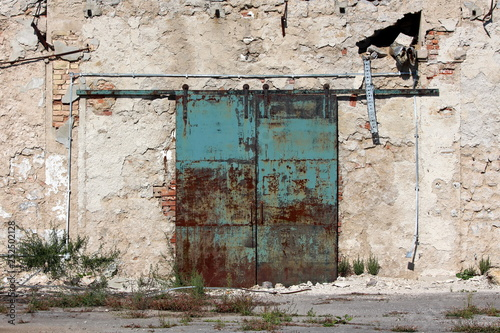 Valokuva  Almost completely rusted blue sliding metal doors mounted on abandoned factory w