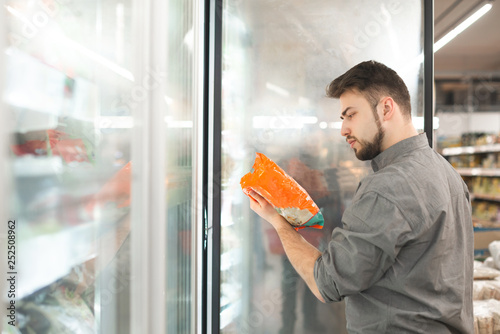 Obraz Buyer standing in the supermarket near the refrigerator holds the package in his hand and reads the label. Man checks the date of production of frozen food in the supermarket. - fototapety do salonu