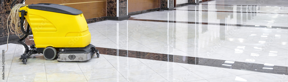 Fototapeta Cleaning machine on marble floor in office, vacuum equipment for cleaning in interior of company or luxury hotel. Concept of professional cleaning service.