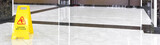 Marble shiny floor in luxury hallway of company or hotel during cleaning. Panorama of washed cleaned floor with sign of caution wet floor. Professional care service of the office interior.
