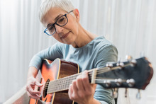 Woman Practicing To Play Guitar