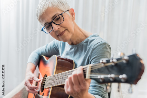 Obraz Woman practicing to play guitar - fototapety do salonu