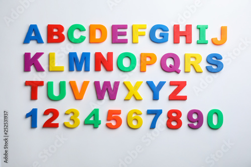 Photo Plastic magnetic letters and numbers isolated on white, top view