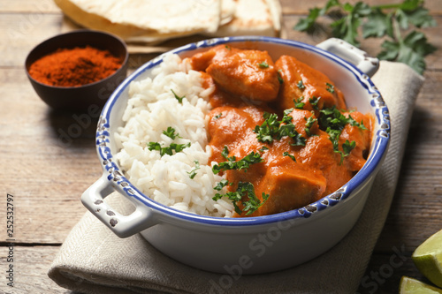 Fotografie, Obraz  Delicious butter chicken with rice in bowl served on wooden table