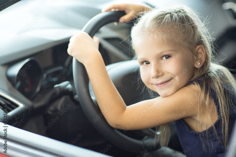 Fototapety, obrazy: Adorable little girl sitting in a car