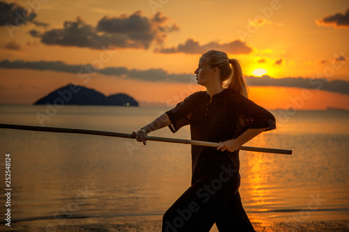 Fotografie, Obraz Young beautiful girl woman blond doing kung fu with bamboo stick on the seashore