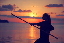 Young Beautiful Girl Woman Blond Doing Kung Fu With Bamboo Stick On The Seashore At Sunset