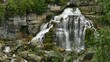 Beautiful waterfall in lush green vegetation setting with flowing water