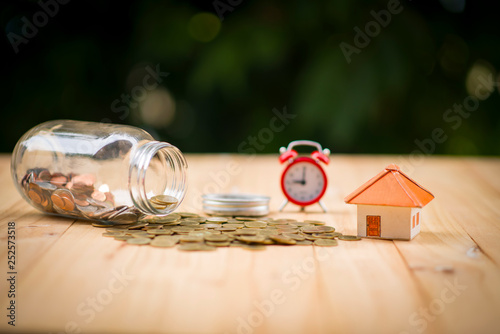 Fototapeta A piggy bank put on the stacking gold coins and blackboard house and clock on the vintage blue background, saving money for buy a new real estate or loan for planned investment in the future concept. obraz