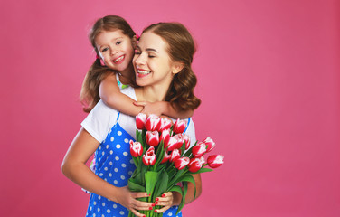 Fototapetahappy mother's day! child daughter gives mother a bouquet of flowers on color pink background.