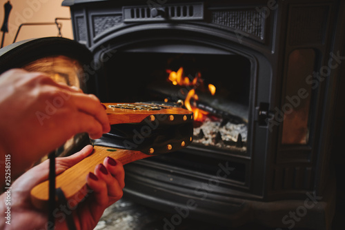 Fireplace bellows in the female palms of the hands. Canvas Print