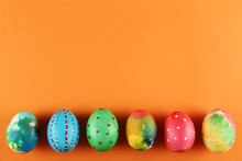 Bunch Of Colorful Tie Dye And Polka Dot Painted Easter Eggs On Bright Orange Paper Background With A Lot Of Copy Space For Text. Top View, Flat Lay, Close Up. Easter Greeting Card Concept.