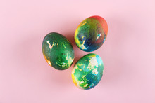 Bunch Of Colorful Tie Dye Hand Painted Easter Eggs On Bright Orange Paper Background With A Lot Of Copy Space For Text. Top View, Flat Lay, Close Up. Easter Greeting Card Concept.