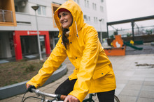 Smiling Girl In Yellow Raincoat Ride Bicycle. Riding Bicycle On Rain Day
