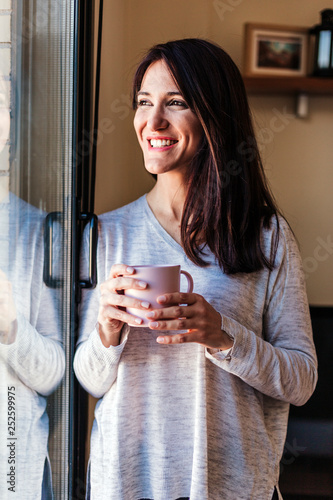 Fotografie, Obraz  Beautiful young woman drinking coffee sitting by the window in the house