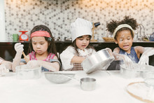 Group Of Kids Are Preparing The Bakery In The Kitchen .Children Learning To Cooking Cookies
