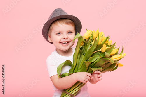 Photo  Adorable smiling child with spring flower bouquet looking at camera isolated on pink