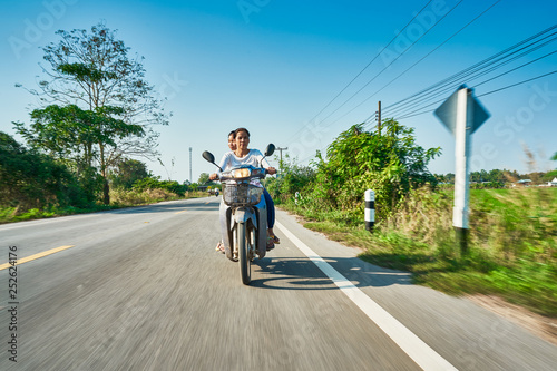 Fotografia, Obraz  thai mother and daughter riding motorbike through rural thailand
