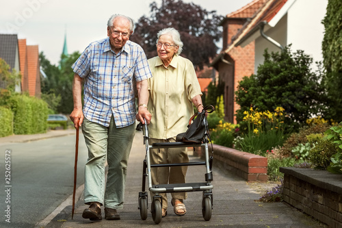 Photo  Elderly couple with walking frame and stick