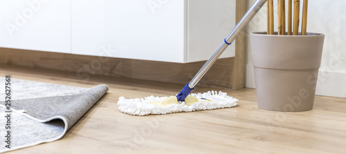 Obraz na plátně Wooden floor with white mop, cleaning service concept