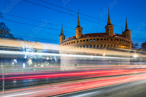 Fototapeta Krakow, Poland, gothic barbican in the night and traffic light trails obraz
