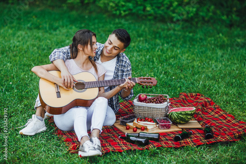 Romantic beautiful couple sitting at the blanket carpet in park and playing guit Wallpaper Mural