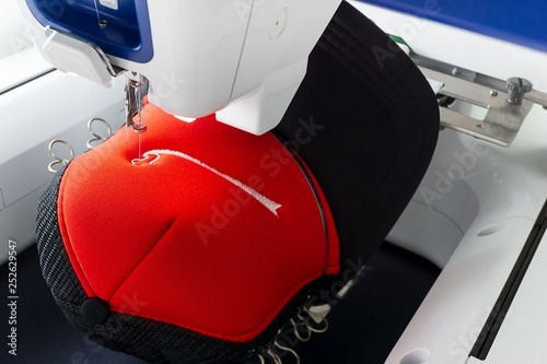 Valokuva  Close up picture of working embroidery machine and red cap