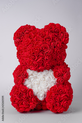 Red teddy bear of foamirane roses. White heart in teddy paws. Stock photo isolated on white background.