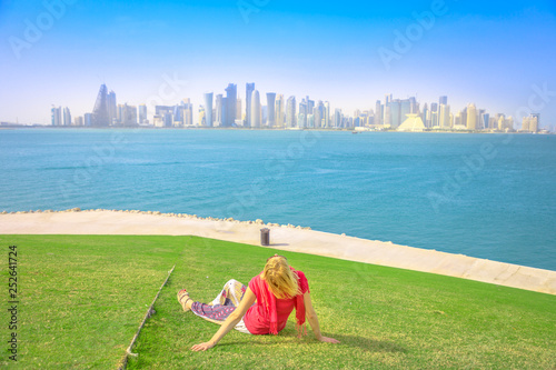 Fényképezés  Caucasian woman sitting on green lawn looks at the views of Doha West Bay in Qatar