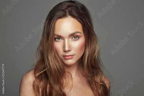 Obraz Portrait of natural sensual woman with long straight hair isolated over gray background - fototapety do salonu