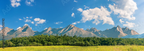 Foto auf AluDibond Himmelblau beautiful sunny day in mountainous countryside. row of trees behind the field. High Tatra mountain ridge in the distance. composite imagery