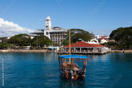 Foto auf Leinwand Sansibar Zanzibar, Tanzania - October, 2014. View to Stone Town, the biggest city of Zanzibar Island. Beautiful day, calm sea and fishermen boats