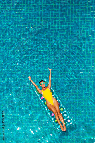 Photo  Gorgeous beautiful lady in sexy yellow bikini swims in a luxury hotel pool on an inflatable mattress