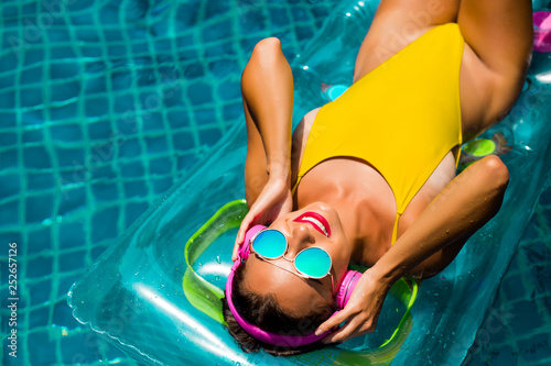 Magasin de musique Amazing beautiful girl in a yellow bikini air mattress swims in the pool of a luxury hotel, summer vacation, happiness, travel, smile joy, listening to music, drinking cocktail
