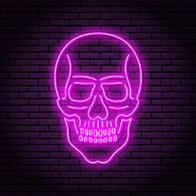 The Image Of The Skull Of Neon Purple Lamps With A Bright Glow On The Background Of A Brick Wall.