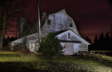 Low Key Old White Barn At Night. Silo, Pine Trees In Background. Colorful Sunset Sky Of Red And Purple. Long Exposure Light Painting.