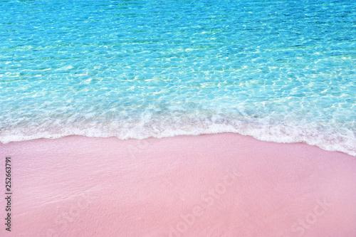 Foto  Soft blue ocean wave on pink sandy beach