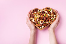 Womans Hands Holding Heart Shaped Bowl With Mixed Nuts On Pink Table Top View. Healthy Food And Snack. Flat Lay.
