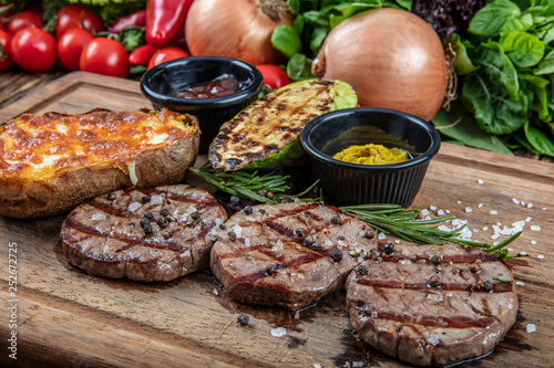 Foto op Canvas Vlees grilled lamb steak served with pumpkin, potatoes, mustard and sauces on wood.