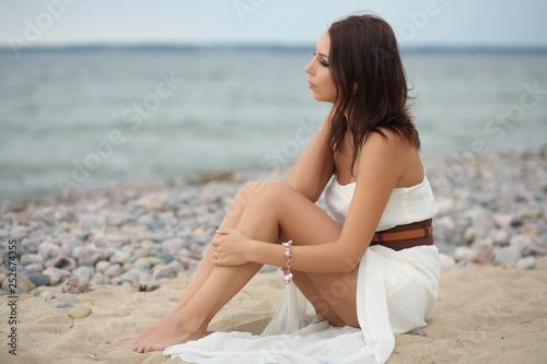 Deurstickers Ontspanning Gorgeous dark-haired girl in dress on sandy beach